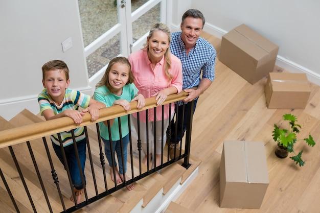 Padres e hijos de pie en la escalera en casa