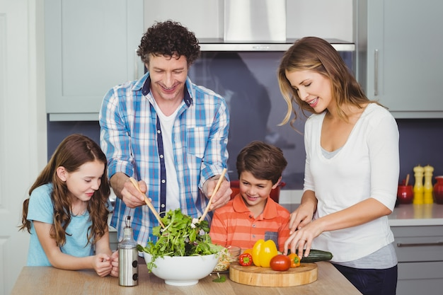 Padres e hijos preparando una ensalada de verduras