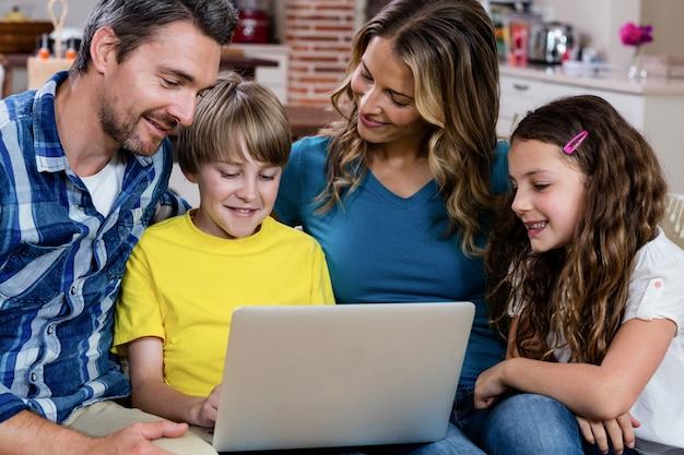 Padres e hijos sentados en el sofá y usando una computadora portátil