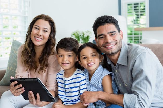 Padres e hijos con tableta digital en la sala de estar en casa