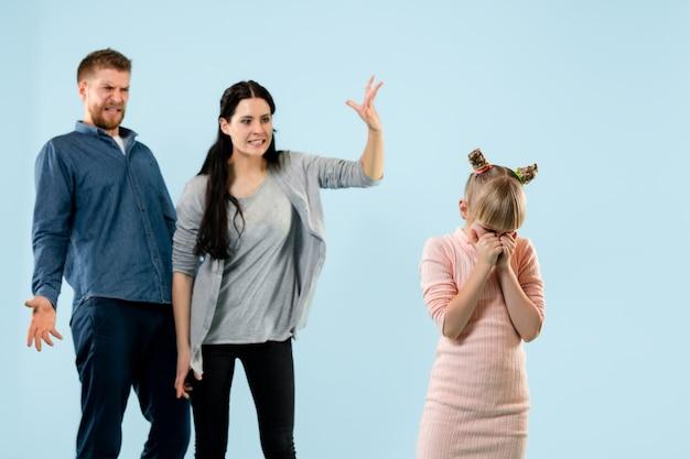Padres enojados regañando a su hija en casa.