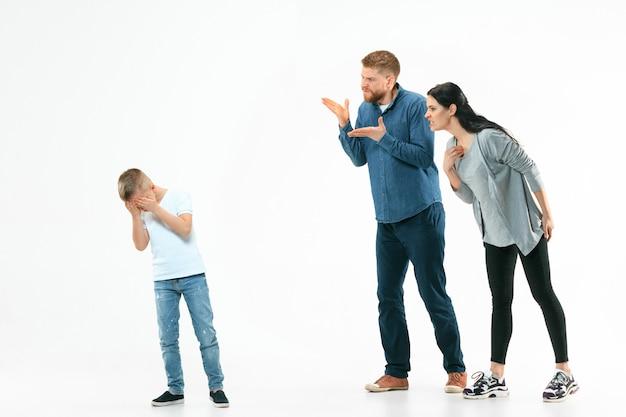Padres enojados regañando a su hijo en casa