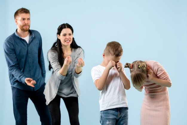 Padres enojados regañando a sus hijos