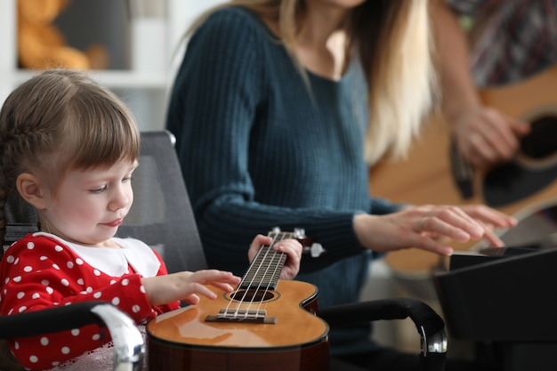 Los padres enseñan al bebé a tocar música ukelele juntos
