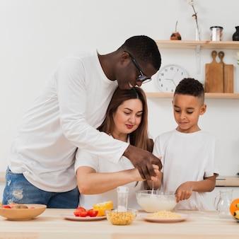 Padres enseñando a hijo a preparar comida