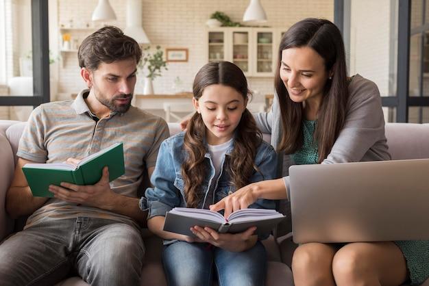 Padres enseñando a niña a leer