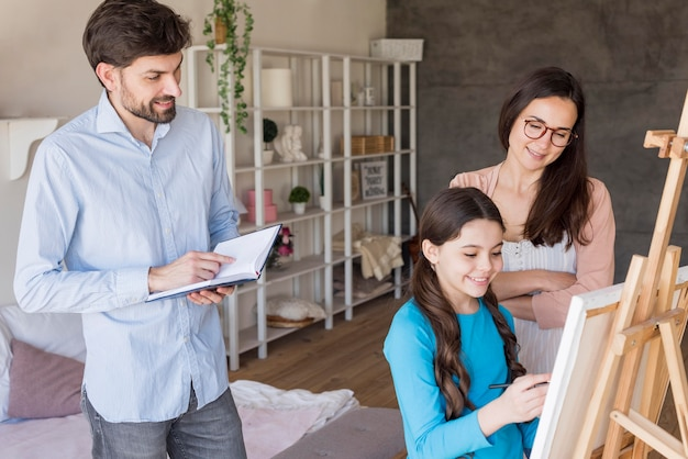 Padres enseñando a niña a pintar