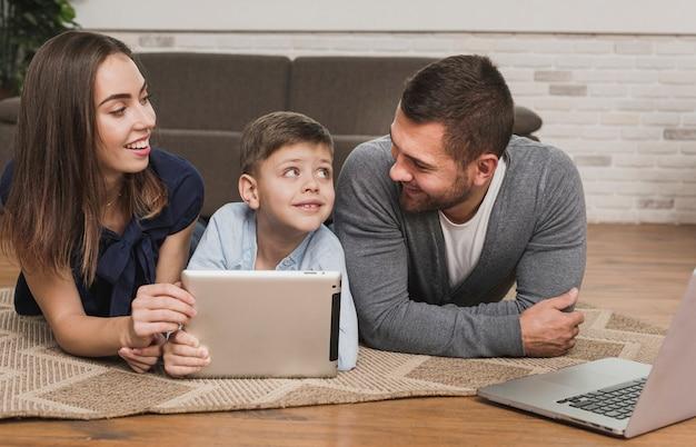 Padres enseñando a su hijo a usar una tableta