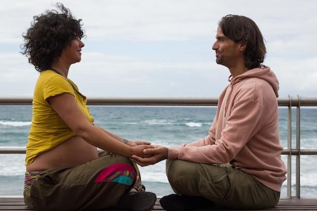 Los padres esperan tomados de la mano sentados en posición de loto en un banco por la playa en las palmas
