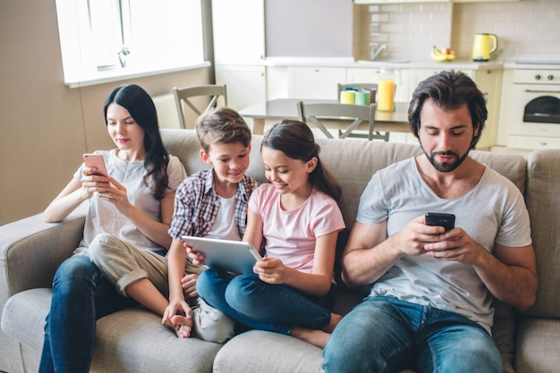 Los padres están sentados en el sofá con los niños y miran los teléfonos. los niños están entre la mujer y el hombre. la muchacha sostiene la tableta en sus manos. miran la pantalla.
