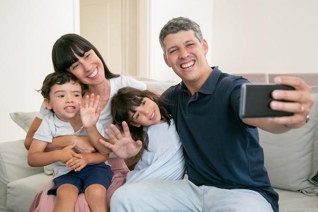 Padres felices abrazando a adorables niños, sentados juntos en el sofá en casa, tomando selfie en el teléfono