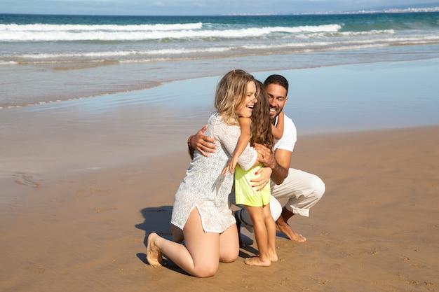 Padres felices abrazando a la pequeña hija en la arena mojada en el mar