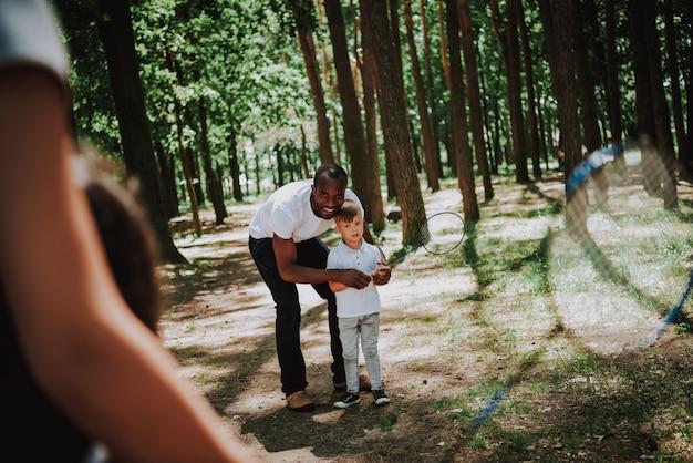 Padres felices enseñan a los niños a jugar al bádminton en el parque