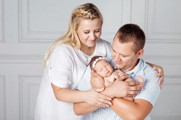 Padres felices con una linda niña recién nacida. mamá, papá y bebé. retrato de familia sonriente con recién nacido en las manos. familia feliz