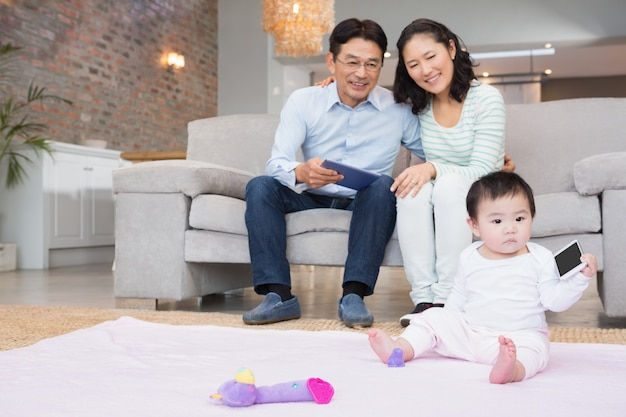 Padres felices mirando a su pequeña hija en la sala de estar