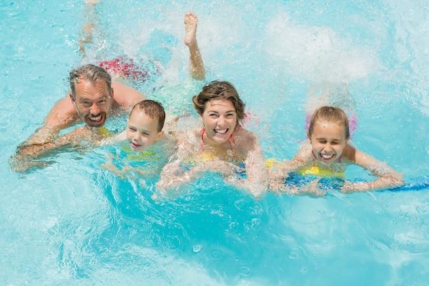 Padres felices y niños divirtiéndose en la piscina