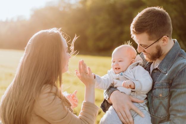 Los padres felices pasan tiempo y juegan con su bebé al aire libre en un día soleado al atardecer