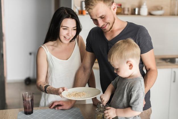 Padres felices que miran al niño pequeño que quita la avena del tarro en la placa