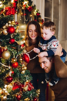 Padres felices que muestran la decoración de navidad en el árbol para el pequeño hijo.