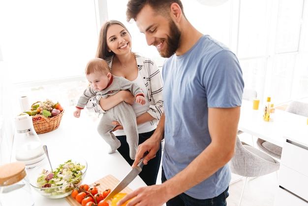 Padres felices con su hijo cocinando en la cocina.