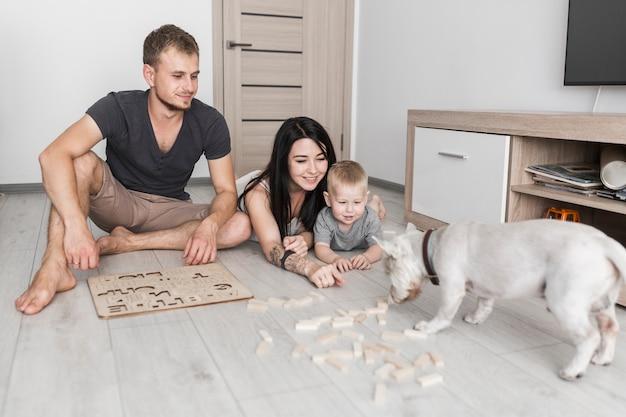 Padres felices con su pequeño hijo mirando perro que huele bloques de madera