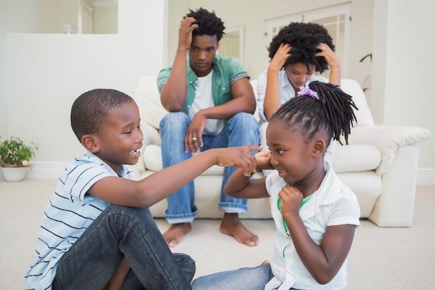 Padres frustrados mirando a sus hijos pelear