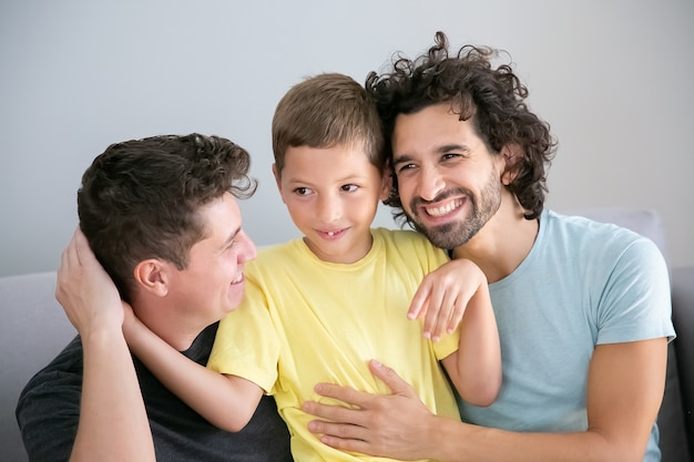 Padres gays alegres e hijo sentados juntos en el sofá y abrazándose. vista frontal. concepto de familia y paternidad feliz