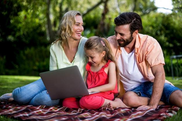 Padres con hija usando laptop en el patio