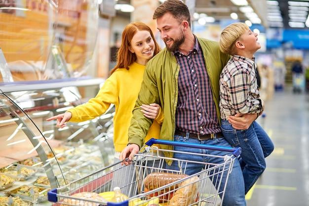 Padres con hijo inquieto en la tienda de comestibles, mujer eligiendo comida para la cena mientras su esposo sostiene a su hijo en las manos, cerca de vitrinas con comida
