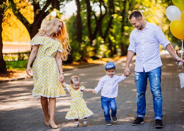 Padres increíbles se divierten con sus dos hijos caminando en el parque