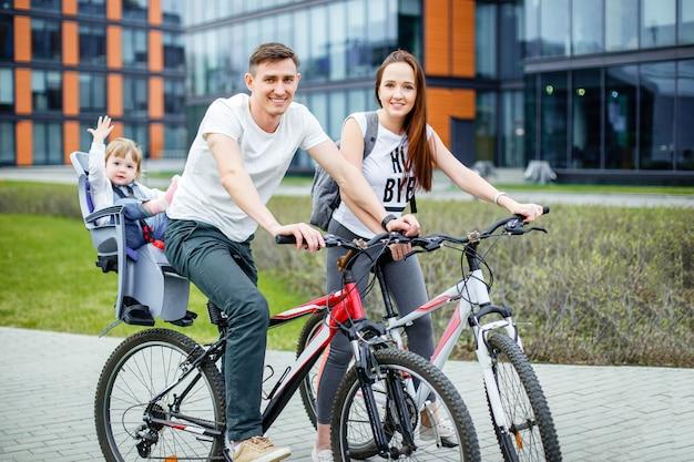 Los padres jóvenes andan en bicicleta con una hija pequeña en las calles de la ciudad