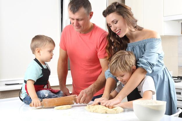 Los padres jóvenes ayudan a los niños a amasar la masa.