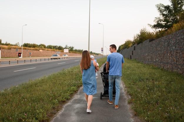 Padres jóvenes caminan con su pequeño hijo en el campo
