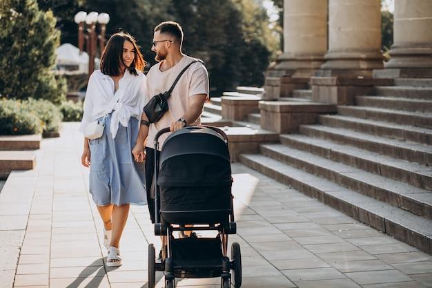 Los padres jóvenes caminando con su bebé en un cochecito