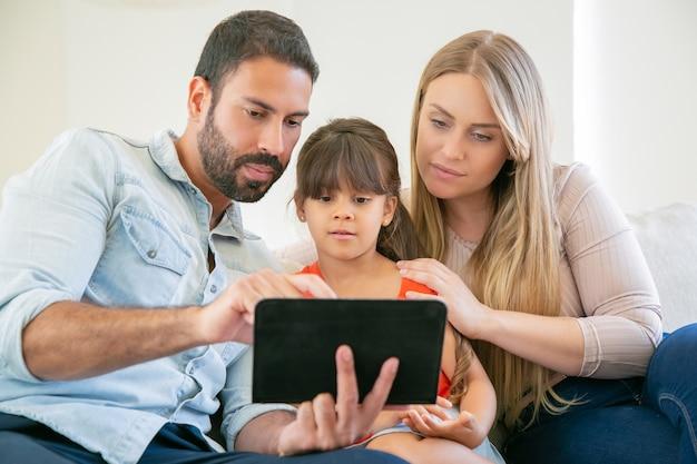 Padres jóvenes enfocados y linda hija sentada en el sofá, usando tableta, mirando la pantalla, viendo videos juntos.