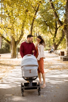 Padres jovenes felices que caminan en el parque y que conducen a un bebé en el carro de bebé