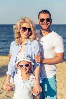 Los padres jóvenes y la hija están mirando a la cámara y sonriendo
