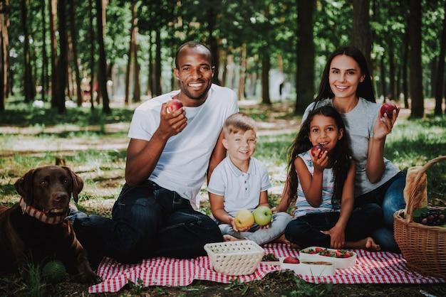 Padres jóvenes hijos y perro picnic en el parque