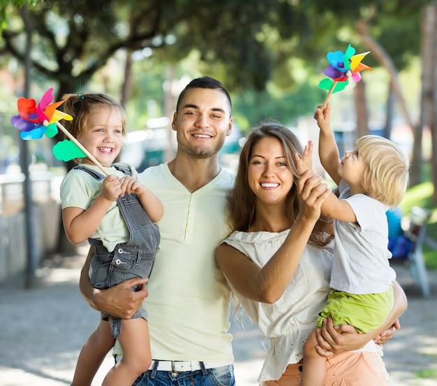 Padres jóvenes con niños jugando molinos de viento