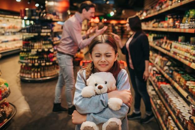 Los padres jóvenes y su hija en la tienda de comestibles. se sienta en el carrito y abraza el oso de juguete. chica mantén los ojos cerrados. los padres se pelean por detrás.