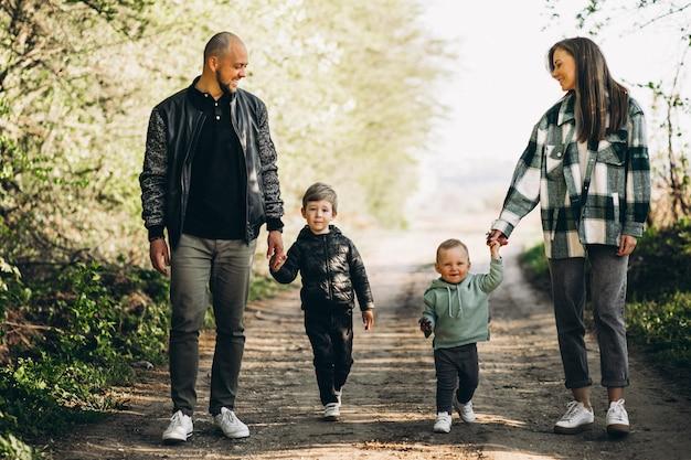 Padres jóvenes con sus hijos en el bosque.