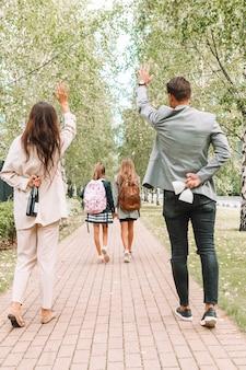 Padres jóvenes con sus hijos en la escuela en otoño. los padres están felices de que los niños finalmente vayan a la escuela. de vuelta a la escuela