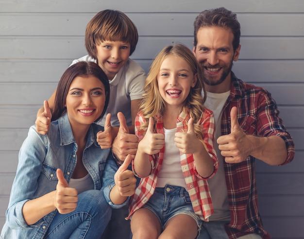Los padres jóvenes y sus hijos muestran los pulgares.