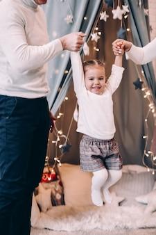 Padres jugando con alegre hijita levantándola con las manos