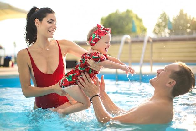 Padres jugando con su bebé en la piscina