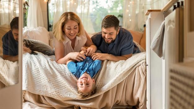 Padres jugando con su hijo en la cama de una caravana