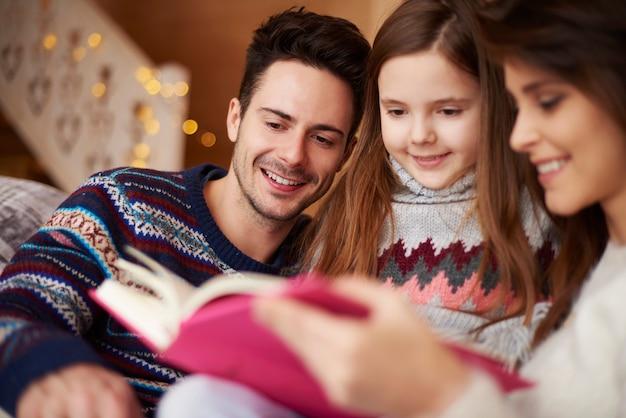Padres leyendo el libro a su hija.