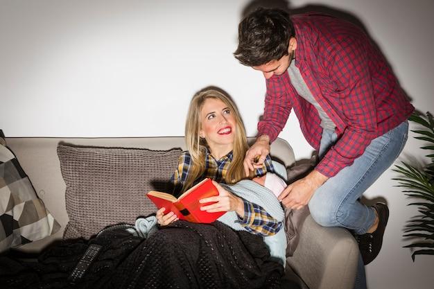 Padres con el libro de lectura del bebé en el sofá