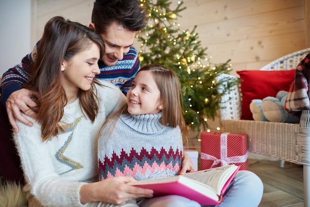Padres con linda chica leyendo cuentos de hadas.