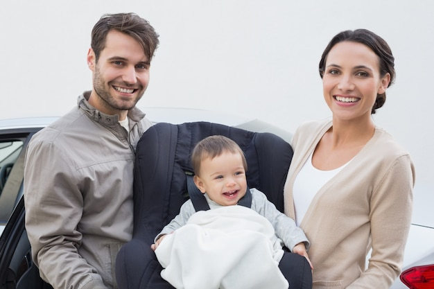 Padres llevando bebé en su asiento